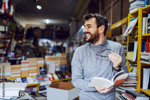 Photographie Handsome caucasian smiling man standing in bookstore with book in hands and looking away