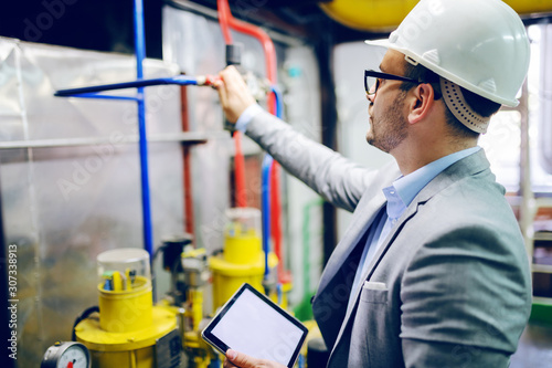 Handsome caucasian supervisor in suit and with helmet on head holding tablet and checking on boiler in factory Fototapet