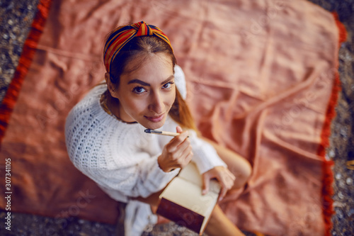 Valokuva Top view of attractive caucasian brunette in sweater and with headband sitting on blanket outdoors and holding pen and diary in hands while looking at camera