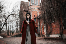 Gothic Autumn Coat. Fabulous Brunette Model. Gothic Model On Abandoned House Background. Victorian Outfit For Halloween. Mysterious Vampire In Dress On Background Of Winter. Fabulous Autumn Look.