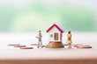 selective focus of miniature angry woman with miniature man and mini house on stack coins over blurred green garden background  for Asset management after divorce concept.