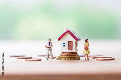 Fototapeta selective focus of miniature angry woman with miniature man and mini house on stack coins over blurred green garden background  for Asset management after divorce concept. obraz