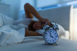 Leinwanddruck Bild - young beautiful woman at home bedroom lying in bed late at night trying to sleep suffering insomnia sleeping disorder or scared on nightmares looking sad worried and stressed