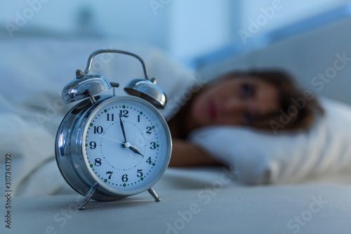 Photo Sleepless and desperate beautiful caucasian woman awake at night not able to sleep, feeling frustrated and worried looking at clock suffering from insomnia in sleep disorder concept