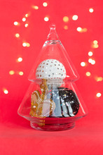 Xmas Composition: Glass Christmas Tree With Gold, White And Black Balls, Bauble On Red Lights Background. Creative Greeting Card In Trend Colors, Copy Space. Minimal Concept