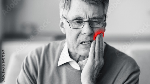 Senior Man Suffering From Toothache Sitting On Couch Indoor, Black-And-White
