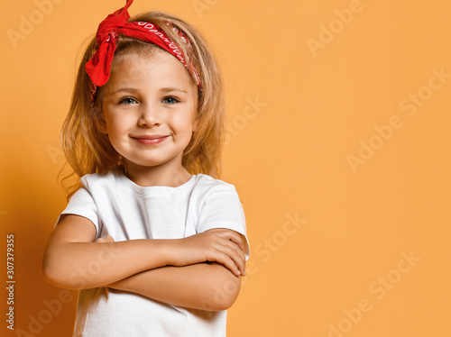 Obraz Kid girl in white t-shirt and red headband is standing at copy space with her arms crossed, looking at us on yellow  - fototapety do salonu