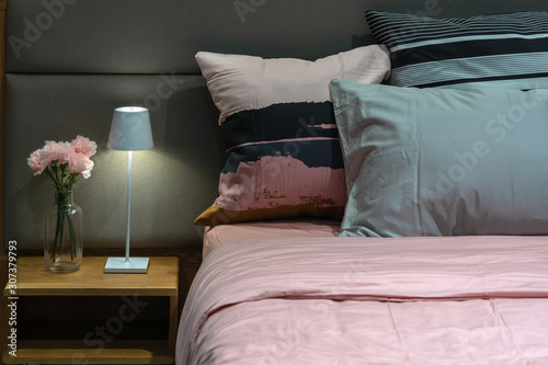 Photo Modern bedside table lamp with green fabric pillows on the cozy bed interior lig