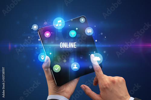 Businessman holding a foldable smartphone with ONLINE inscription, social media concept