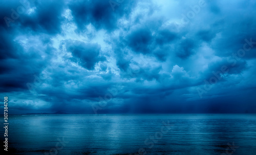фотография Dramatic stormy dark cloudy sky over sea, natural photo background