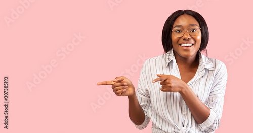 Smiling Afro Woman Pointing Fingers Aside Standing Over Pink Background