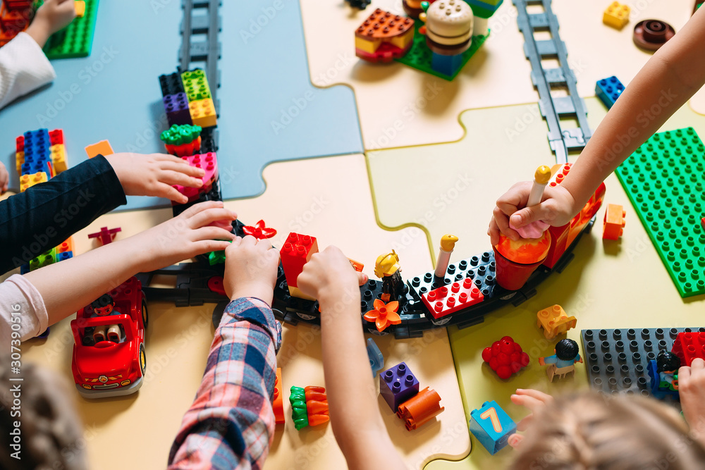 Fototapeta Educational toys for preschool and kindergarten child. Child playing with constructor blocks at class.