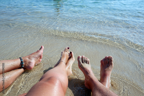 Two pair of legs of young women and one pair of legs of a man rest and relaxed at the beach Wallpaper Mural