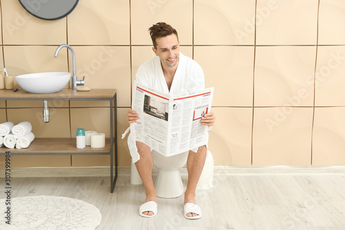 Photo Handsome man with newspaper in restroom
