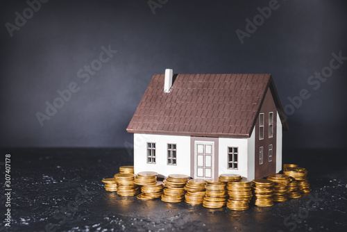 Fotomural  Model of house and money on table. Concept of buying new property