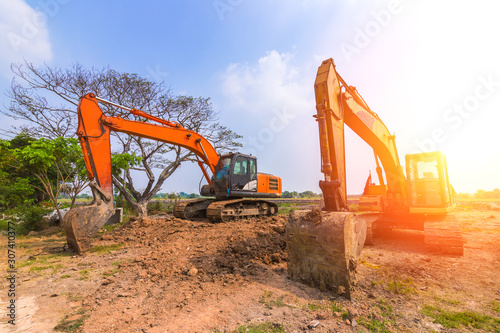 The orange backhoe is on the ground. Canvas Print