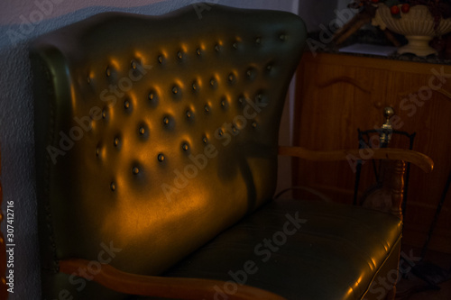 image of a vintage armchair with buttons lit by the firelight of a fireplace in Canvas Print