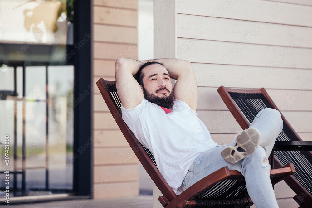 Valokuva Happy young stylish hipster man with beard resting sitting on the lounge beside the hotel