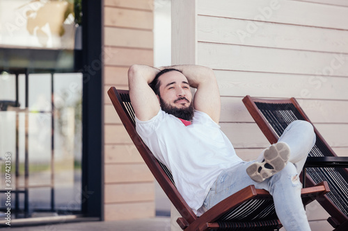 Obraz na plátne Happy young stylish hipster man with beard resting sitting on the lounge beside the hotel