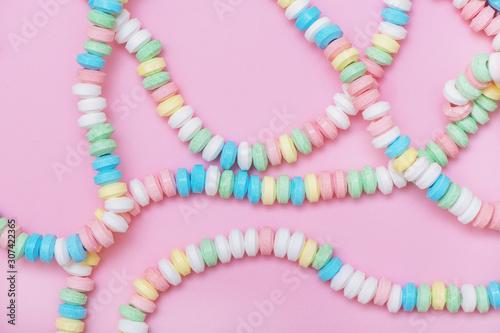 Obraz na plátně Candy necklace on pink pastel colored background.