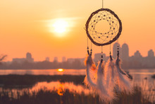 Dream Catcher Against The Background Of The Present In The Form Of A City In The Background, And The Future In The Foreground. Refusal Of City Vanity. Downshifting Philosophy