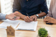 Young asian man signing a contract for buying house in office of estate agent and Real estate agent giving key from new house to young couple in office