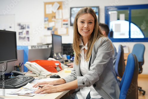 Portrait of businesswoman in office sitting at desk Canvas Print