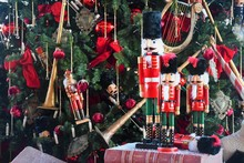 Soldier Nutcracker Wooden Statue Standing In Front Of Decorated Christmas Tree On An Old Book