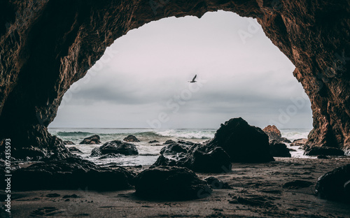Fotografija View of pelican bird flying in dark sky above stormy ocean sea with waves crashing against rock from within inside beach cave bay looking out through entrance opening