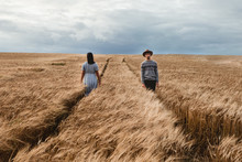 Woman In Checked Dress And Man In Sweater And Hat Walking In Opposite Directions On Parallel Footpaths Among Boundless Brown Scottish Field With Cloudy Sky On Background