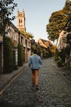 Back View Of Man Walking On Narrow Street In Town