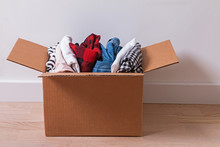 Cardboard Box Full Of Clothes Standing On The Floor.