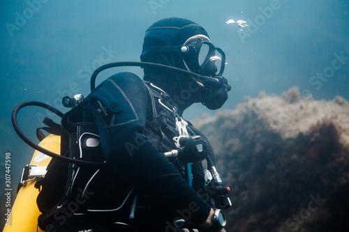Canvas instructor de buceo buceando y esperando durante una instrucción para curso de submarinismo dentro del mar, playa en Palamós, España