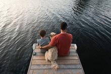 Father And Son Sitting On End Of A Dock On A Lake With Their Dog.