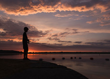 Silhouette Of A Boy Fishing On The Edge Of A Lake At Sunset.