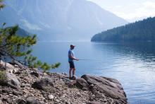 Man Standing On Rocks Fishing At A Mountain Lake