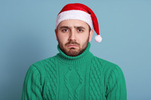 Caucasian Bearded Man Wearing Stylish Green Sweater And Santa Hat Isolated Over Blue Background, Having Upset Facial Expession, Looks Sad, Posing With Pouty Lips, Being In Good Mood. People Concept.