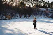 Little Girl Plays On Frozen Lake Covered In Snow