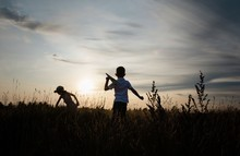 Silhouette Of Siblings Playing With Paper Planes Outside At Sunset