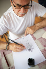 Senior Man Drawing With Pen.