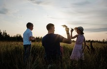 Father Playing With Paper Aeroplanes With Son And Daughter At Sunset