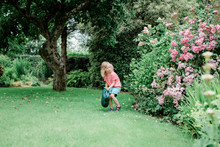 Young Girl Watering Her Country Garden In England With Watering Can