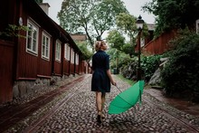 Woman Walking On A Cobbled Street With An Umbrella Looking At The Rain
