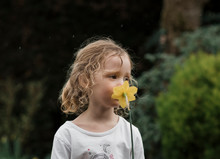 Young Girls Standing In The Rain Smelling A Daffodil In The Garden