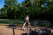 A Man Pulls A Heavy Tire With A Rope In An Outdoor Obstacle Course