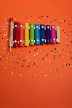 Wooden Xylophone In Rainbow Colors For Children An Isolated On Orange. Paper Colorful Musical Notes Surrounding