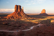 Sunset light hits the iconic rock formations in Monument Valley, AZ