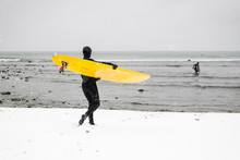 Woman Getting Ready To Surf On A Snowy Day