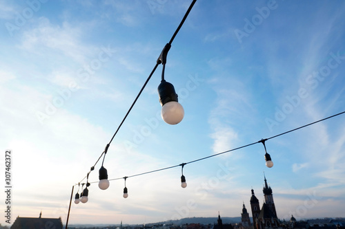 Fotomural garland of large bulbs on the terrace for decoration on holidays or at night against a blue sky and old buildings background with small white clouds