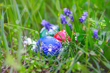 Happy Easter! Eco Friendly Traditional Wooden Painted Easter Eggs In Grass With Grape Hyacinth Flowers Outdoors, Close-up